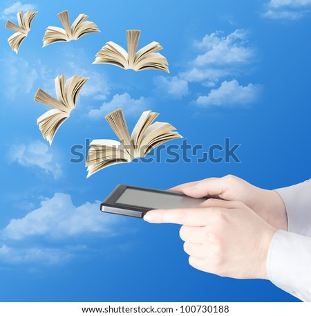 Hand holding electronic book and opened books flying to the sky (education concept) - stock photo