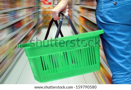 Hand holding empty shopping basket - Shopping concept - stock photo