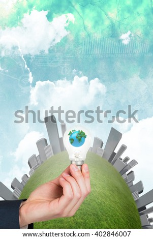 Hand holding environmental light bulb against green and blue sky