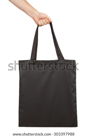 Hand holding fabric tote bag isolated on white background - stock photo