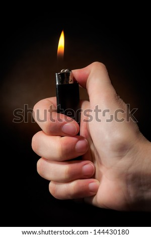 Hand holding fire lighter isolated on black background.