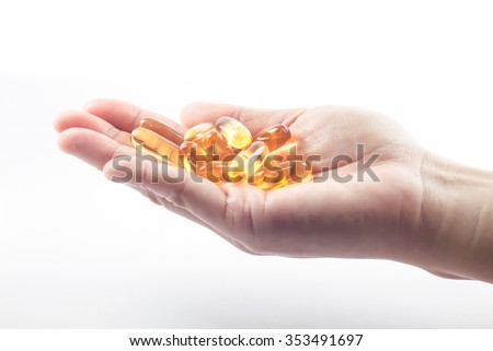 Hand holding fish oil capsules on white background, stock photo