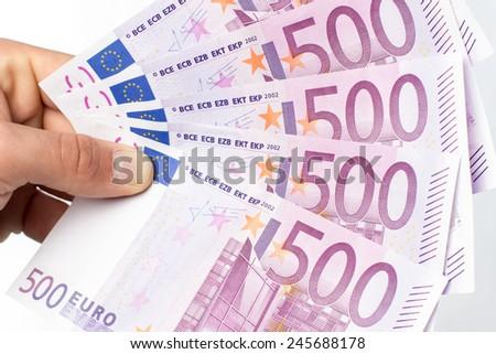 Hand holding five hundred euros bills against white background - stock photo