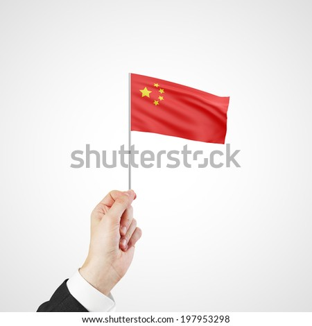 hand holding flag of China on gray background - stock photo