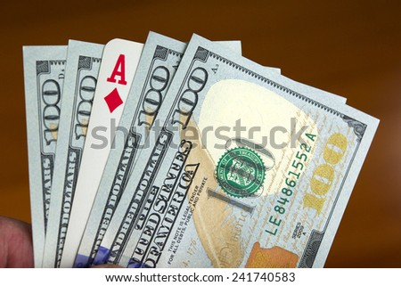 Hand holding four new one hundred dollar bills and an As of diamonds card, like if it was a poker hand.