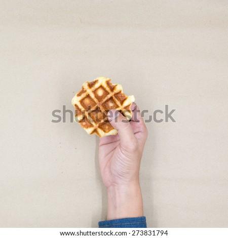 Hand holding fresh and tasty Waffle - stock photo