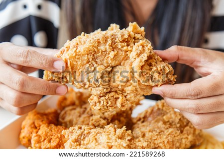 Hand holding Fried chicken and eating in the restaurant - stock photo