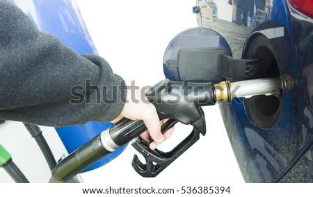 hand holding fuel pump at gas station in car