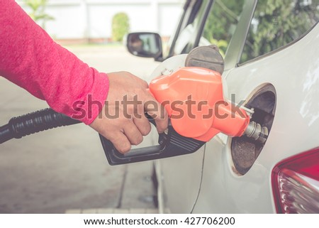 Hand holding fuel pump nozzle and refilling car,Vintage concept - stock photo