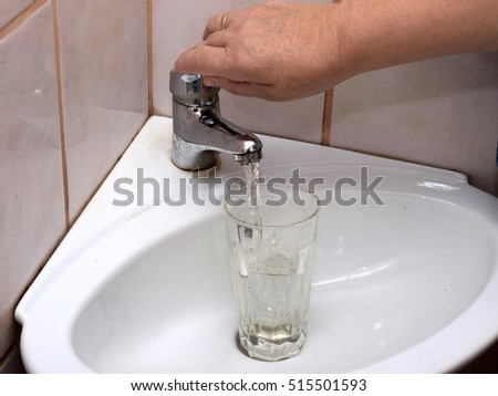 Hand holding glass in sink and fill it with water from crane.
