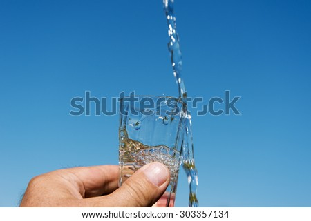 Hand holding glass of water.