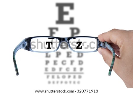 Hand holding glasses and reading eye chart test vision on white