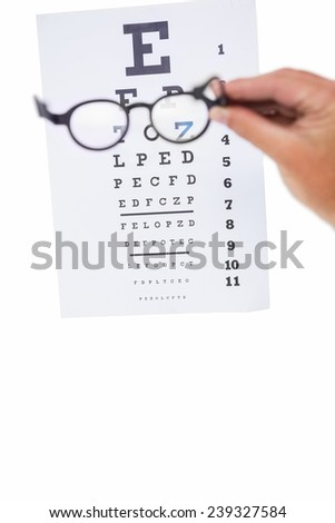 Hand holding glasses for a eye test on white background