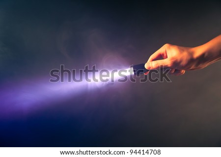 hand holding glowing pocket torch light - stock photo