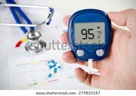Hand holding glucometer. Stethoscope and pills in background