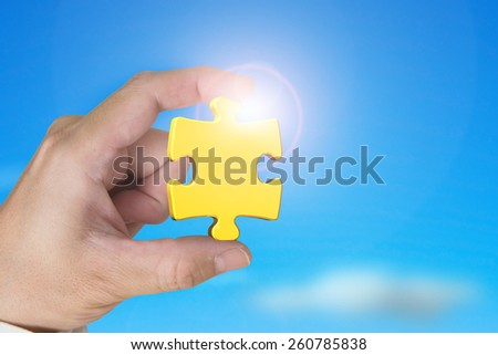 Hand holding gold jigsaw puzzle piece with blue sky sunlight background