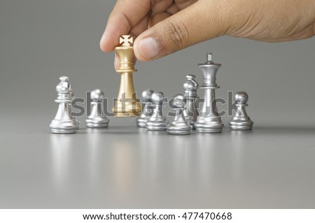 Hand holding Golden Queen with his pawn on the board