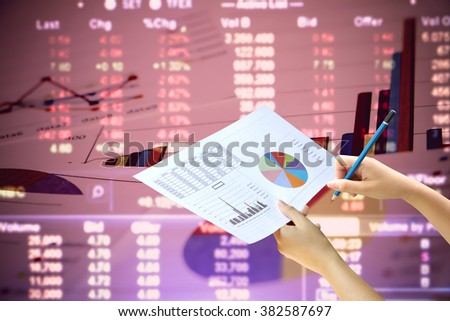 hand holding graph paper with blur stock market number background