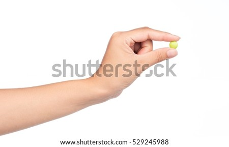 hand holding green chocolate coated candy isolated on white background