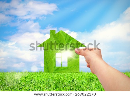 hand holding green house with field and blue sky background. Eco house concept  - stock photo