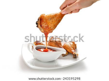Hand holding grilled chicken leg dipping in ketchup - stock photo