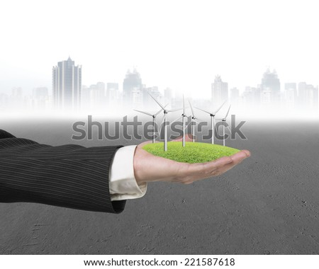 hand holding group of windmills on grass with city buildings background - stock photo