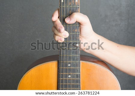 hand holding guitar with background - stock photo