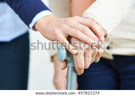 Hand holding hand of senior woman with a cane