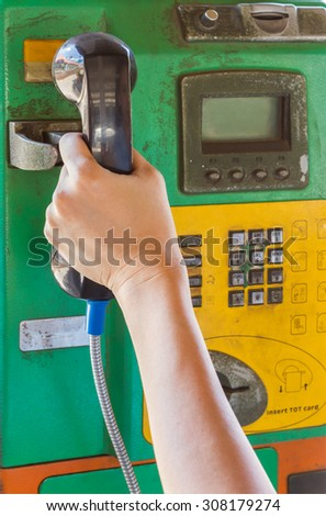 Hand holding handset of a public telephone background.