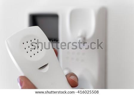 Hand holding headphone of entry phone. - stock photo