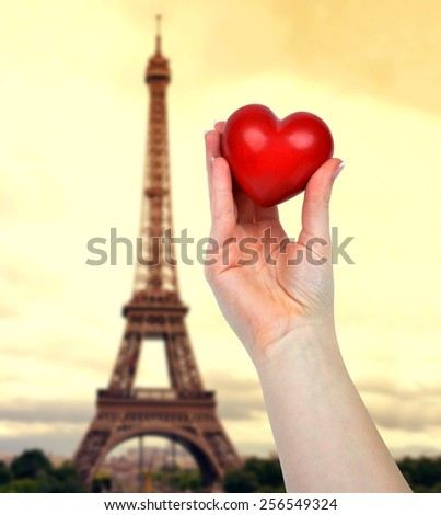 Hand holding heart. In the background Eiffel tower at sunset
