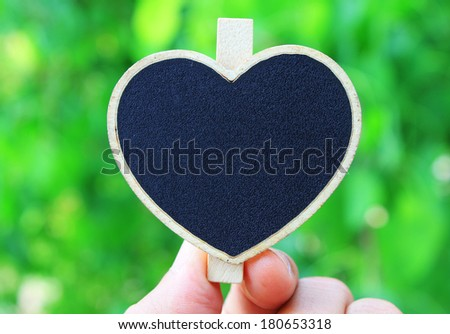 hand holding heart shape wooden sign - stock photo