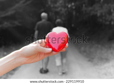 Hand holding heart with couple in a background - stock photo
