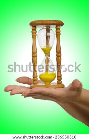 Hand holding hourglass on white - stock photo