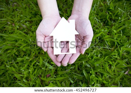 Hand holding house against green field, spring time.
