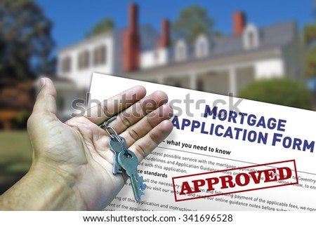 Hand holding house key with approved mortgage form background. - stock photo