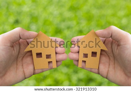 Hand holding house on green grass