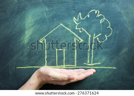 Hand holding house secure, chalk drawing on black board - stock photo