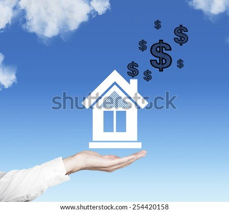 hand holding house with dollars on sky background - stock photo