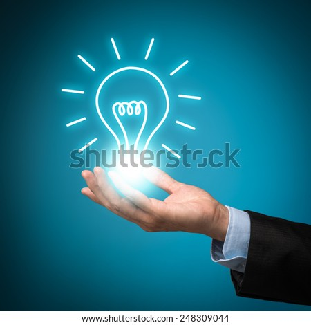 Hand holding idea lightbulb. Bulb light on Business man hand on blue background - stock photo