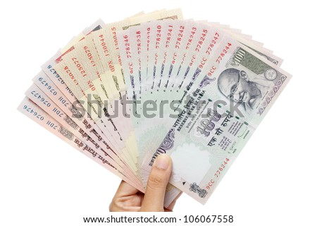 Hand holding Indian rupee notes against white - stock photo