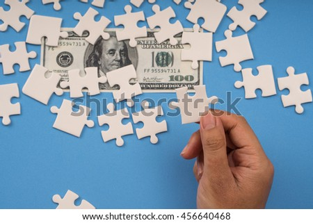 hand holding jigsaw, banknote money on background - stock photo