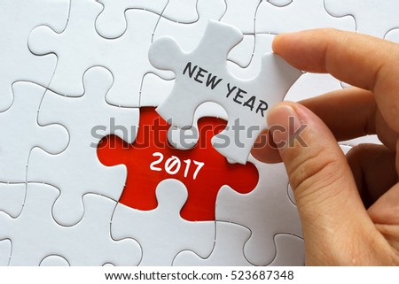 Hand holding jigsaw puzzle with word NEW YEAR 2017.