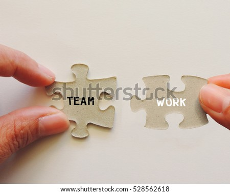 "Hand holding jigsaw puzzle with word""TEAMWORK"""