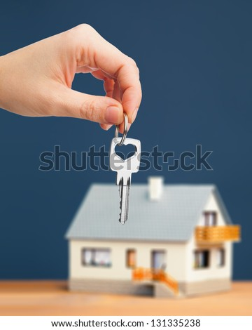 hand holding key against house background