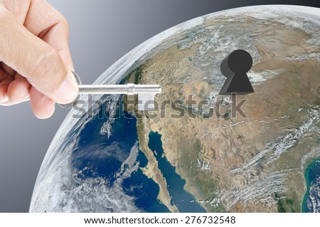 Hand holding key on earth background , Elements of image are furnished by NASA - stock photo