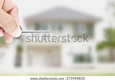 Hand holding key on house background - stock photo