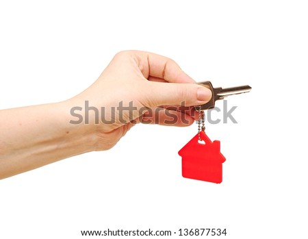 Hand holding key with a key-chain in the shape of the house. House key on the white background - stock photo