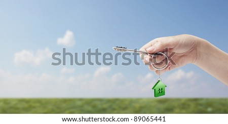 Hand holding key with a keychain in the shape of the house. House key on background of nature - stock photo