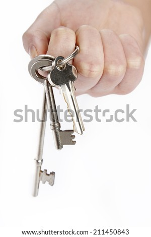 Hand holding keys in front of plain background